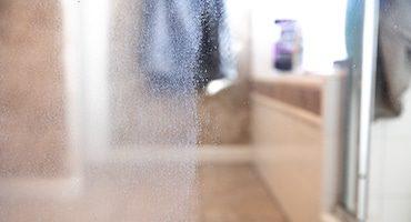 Restauration de vitre de douche avec traces d'eau calcaire qui ressemblent à des traces de pluie.