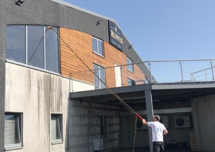 Laveur de vitres qui nettoie une baie vitrée avec une perche télescopique et arrivée d'eau ultra-pure